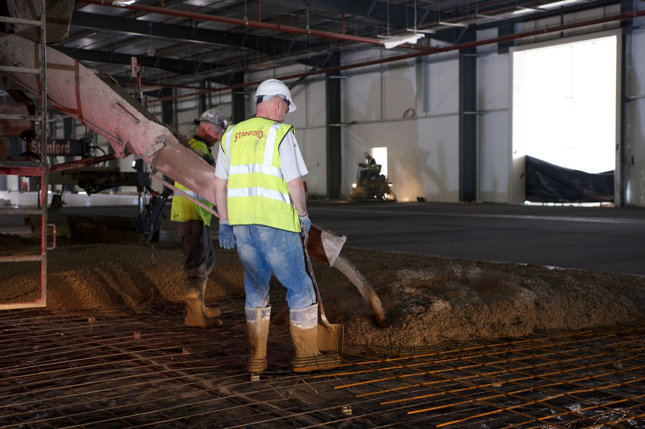 Construction workers pouring concrete on wearhouse floor