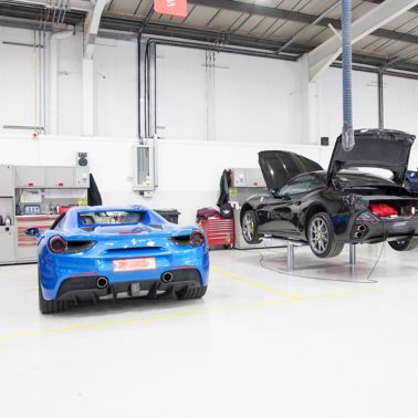 Ferrari cars in repair workshop parked on smooth and seamless floor