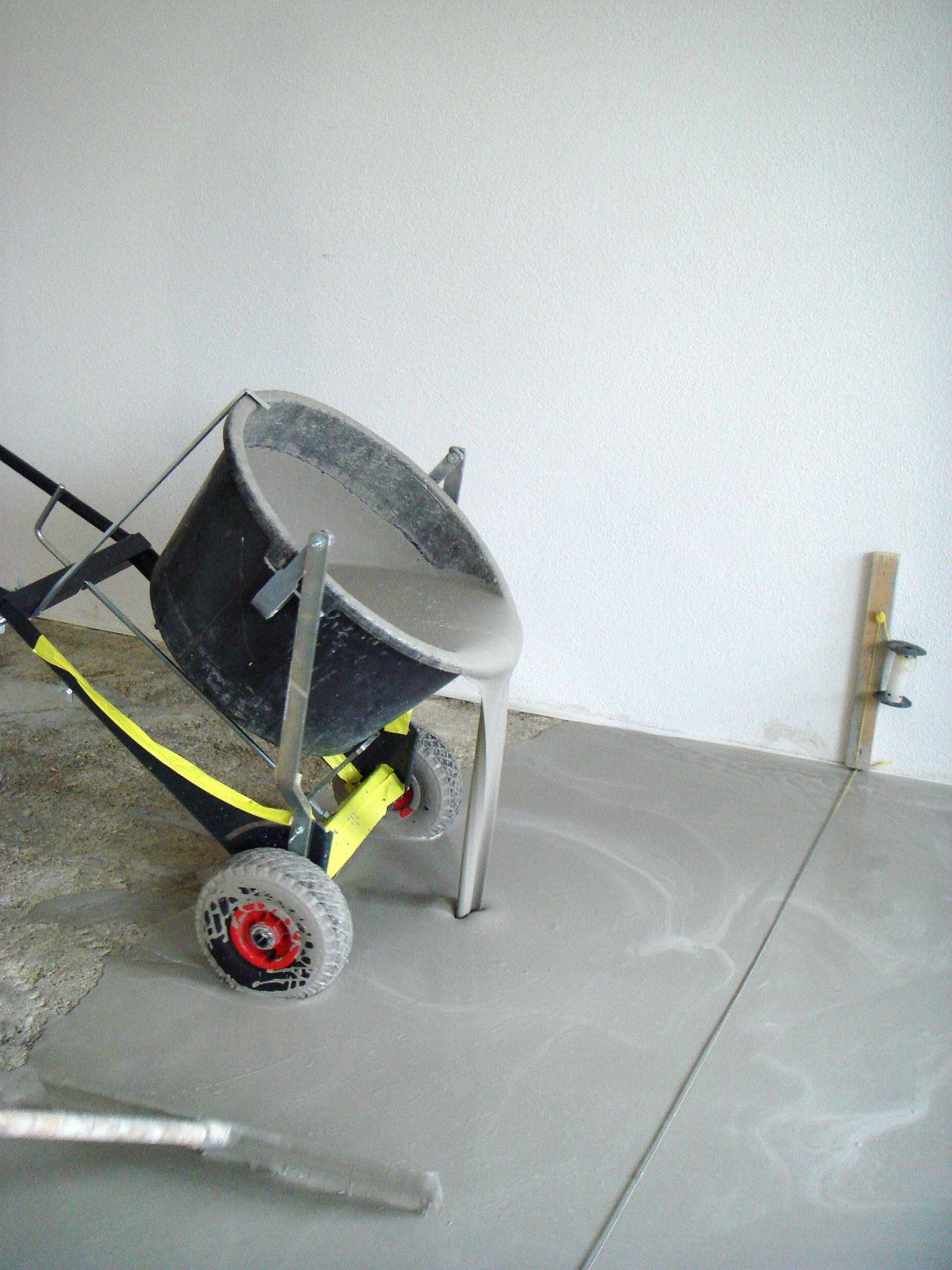 Sika applicator applying floor leveling from yellow bucket to shiny floor