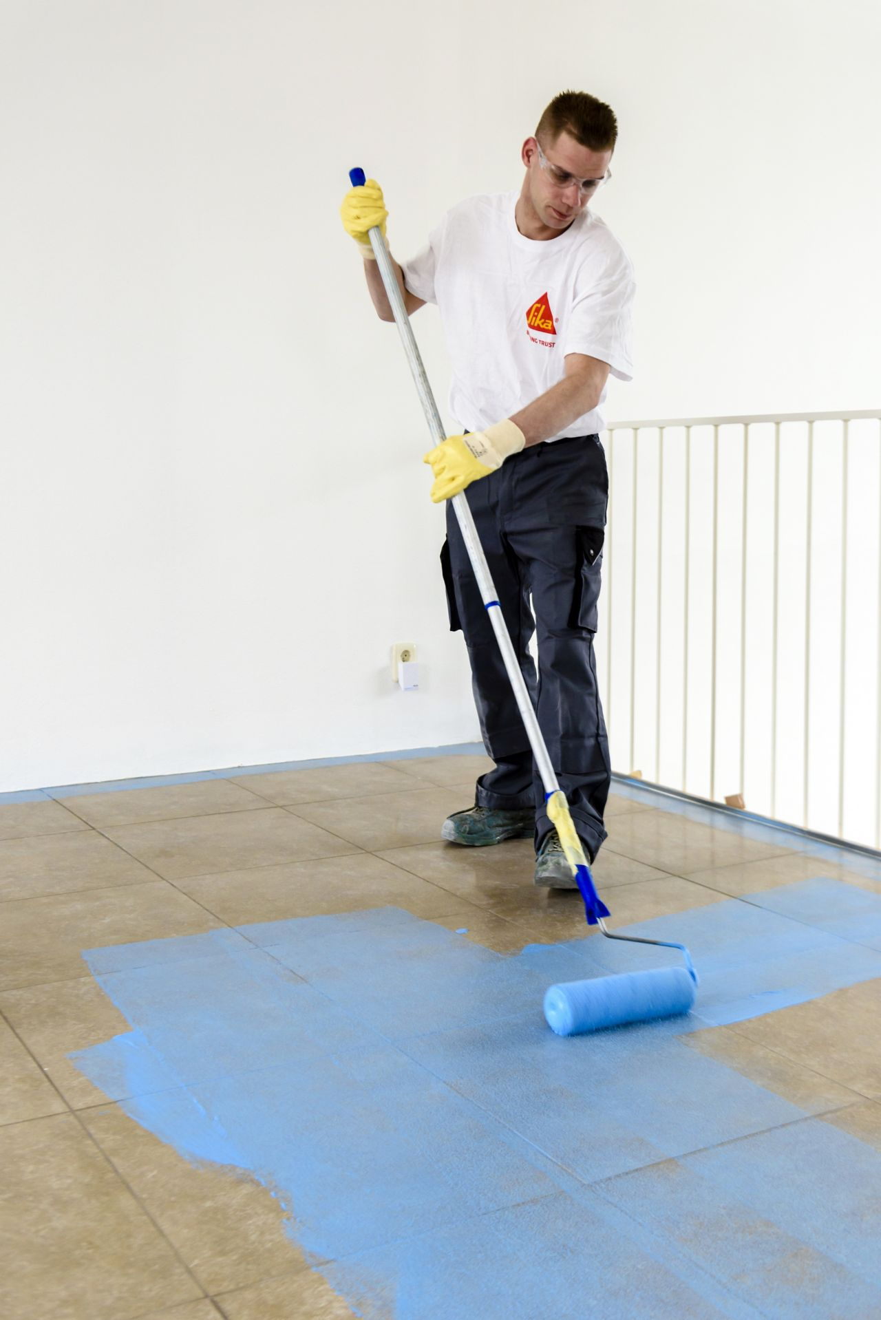 Sika applicator applying blue primer coat to floor tiles