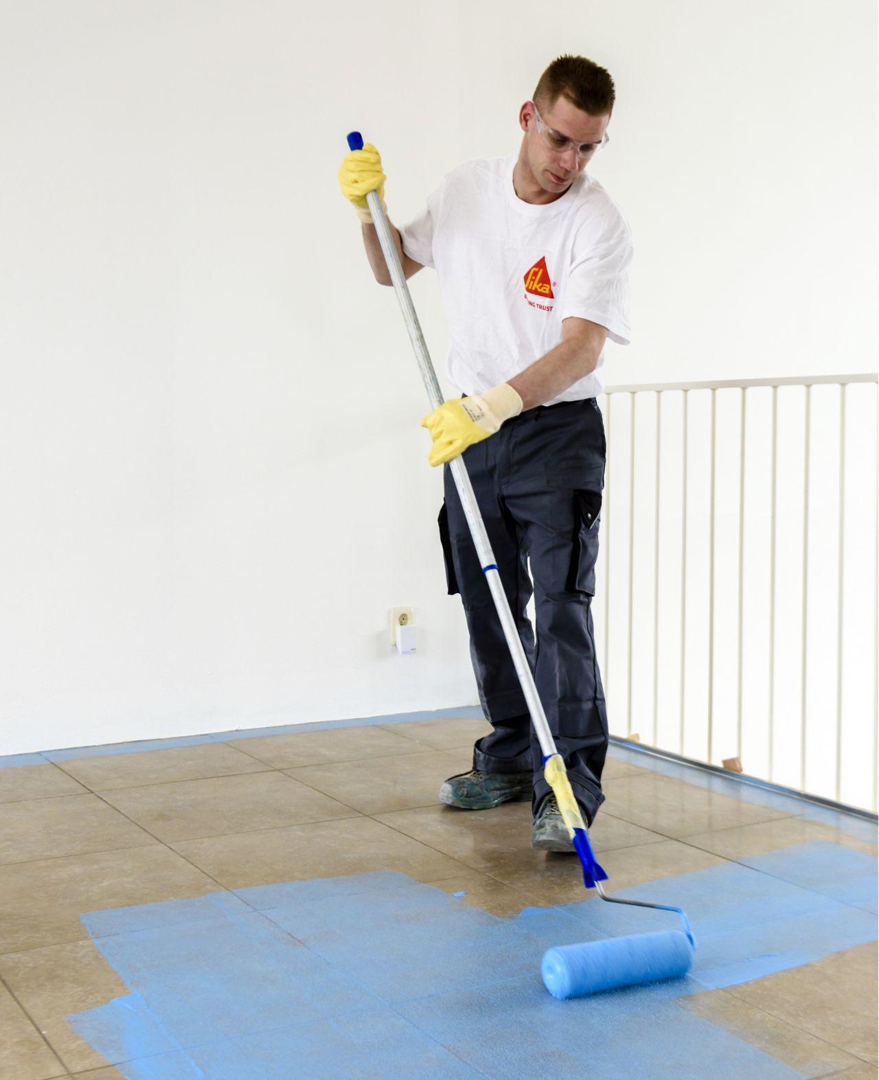 Sika applicator applying blue primer coat to floor tiles