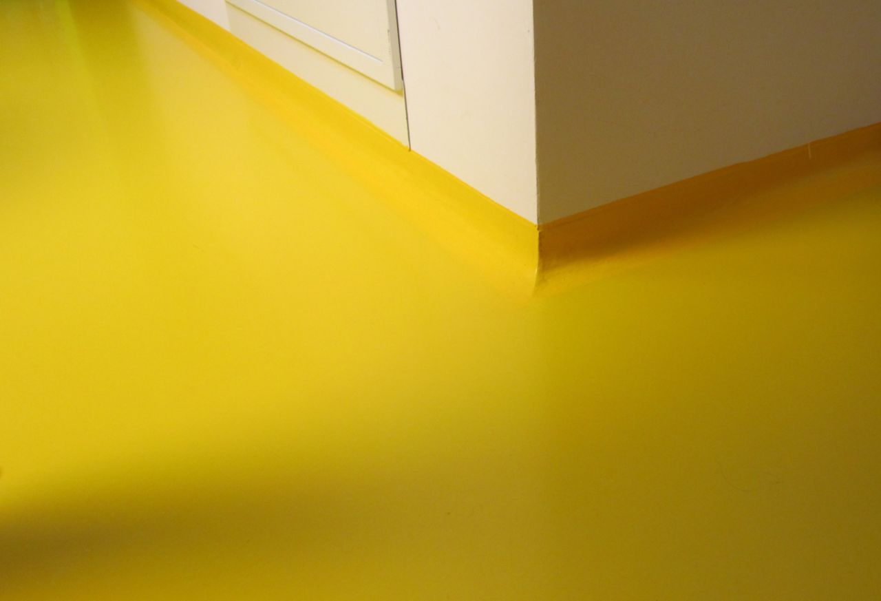 Seamless coving transition detail at floor to wall connection in yellow floor