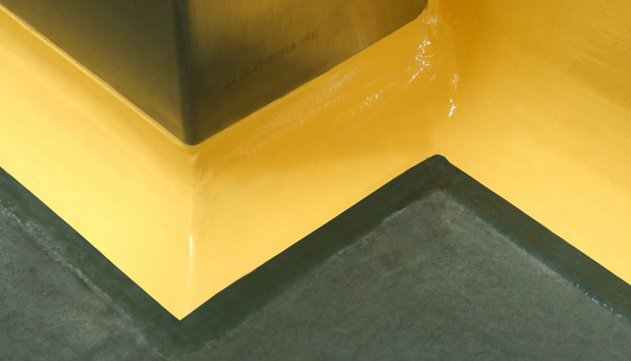 Yellow floor to wall coving detail at seamless joint between wall and floor with Sikagard