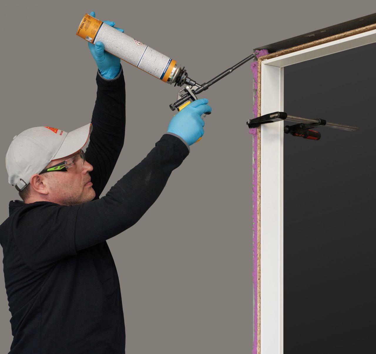 Man applying fire resistant Sika foam