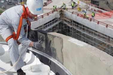 Man applying mortar over carbon grid reinforcement on FRCM wall with bridge in background