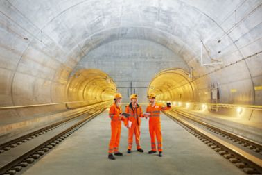 Three construction workers talking inside Gotthard Tunnel in Switzerland