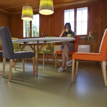 Sika ComfortFloor® green floor with lady drinking tea at dining room table