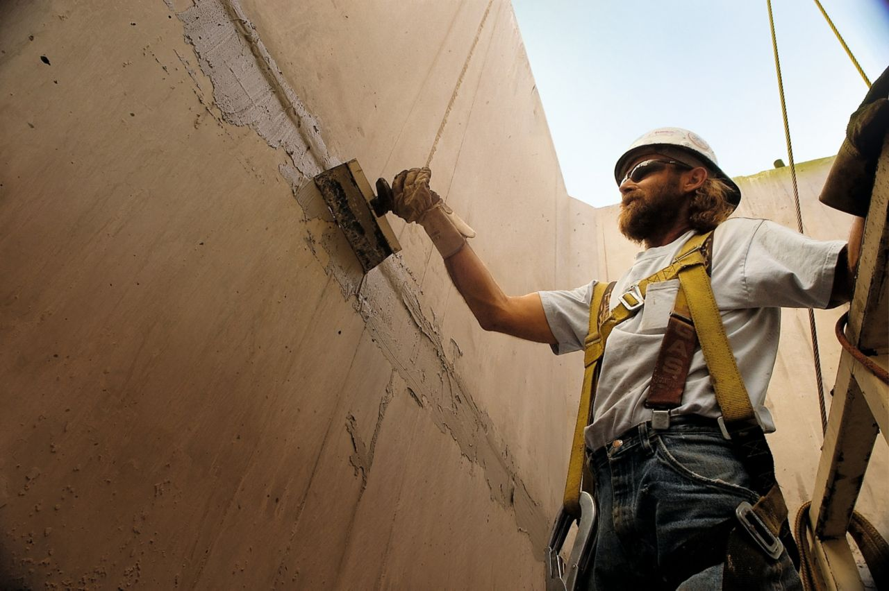 Man applying concrete repair mortar at Hoover Dam bypass bridge project