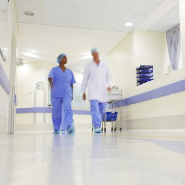 Doctor and nurse walking through hospital with wall and floor coatings