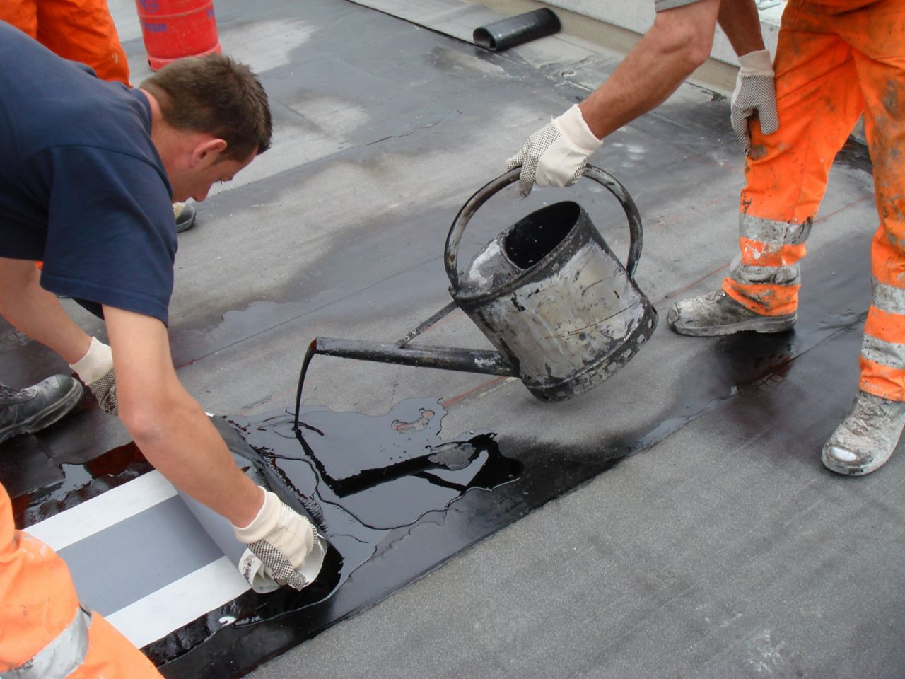 Two workers applying hot melted bitumen membrane