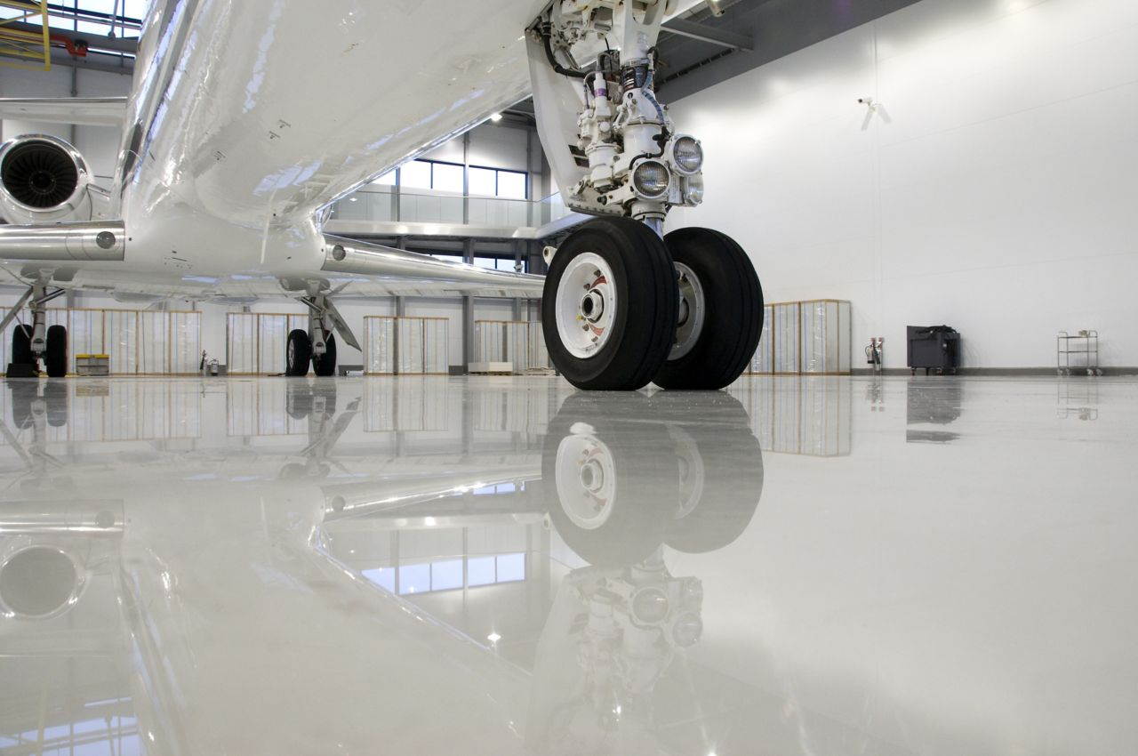 Plane wheel on industrial floor coating with Sikafloor high performance flooring system in aircraft hangar