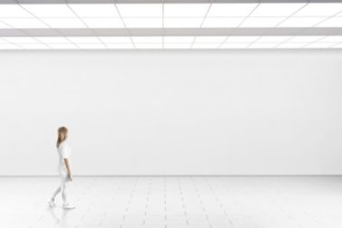 Woman walking in front of a white wall