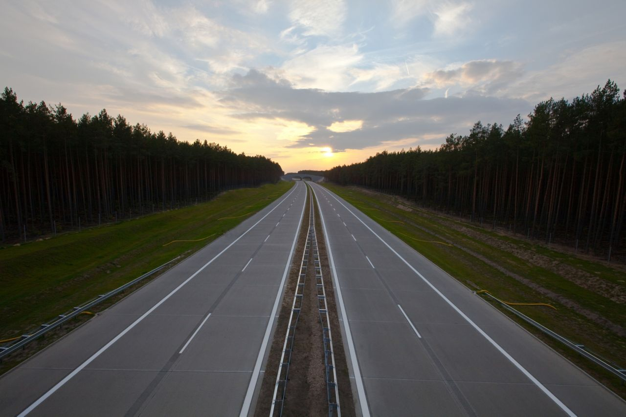 Highway road in Poland with forest and sunset