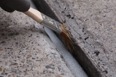 Hand applying joint sealant by brush to concrete road joint