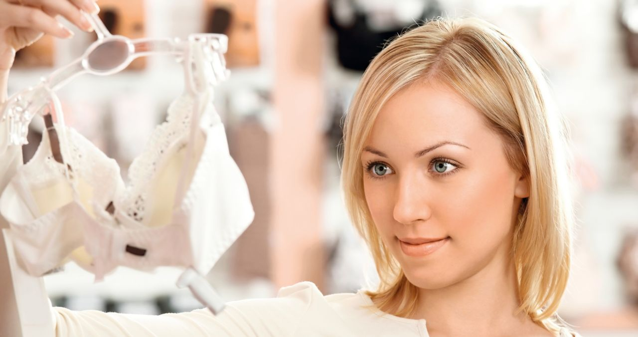 Woman looking at bra made of adhesive bonded textile