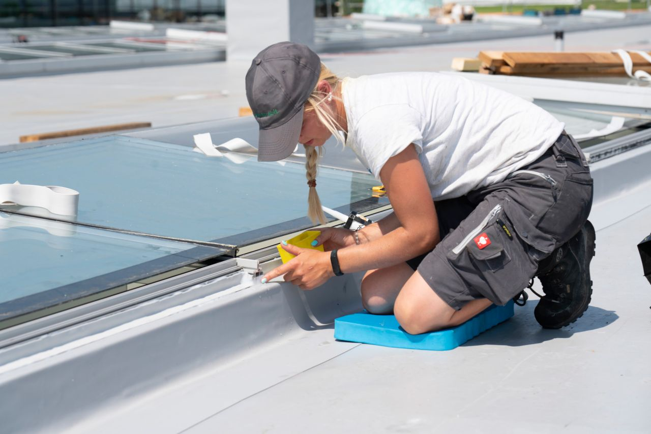 Construcion lady applying Sarnafil AT during Leister Technologies roof refurbishment