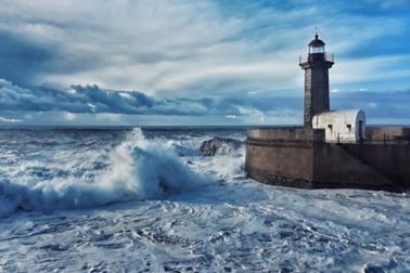 Lighthouse at sea with waves crashing and clouds