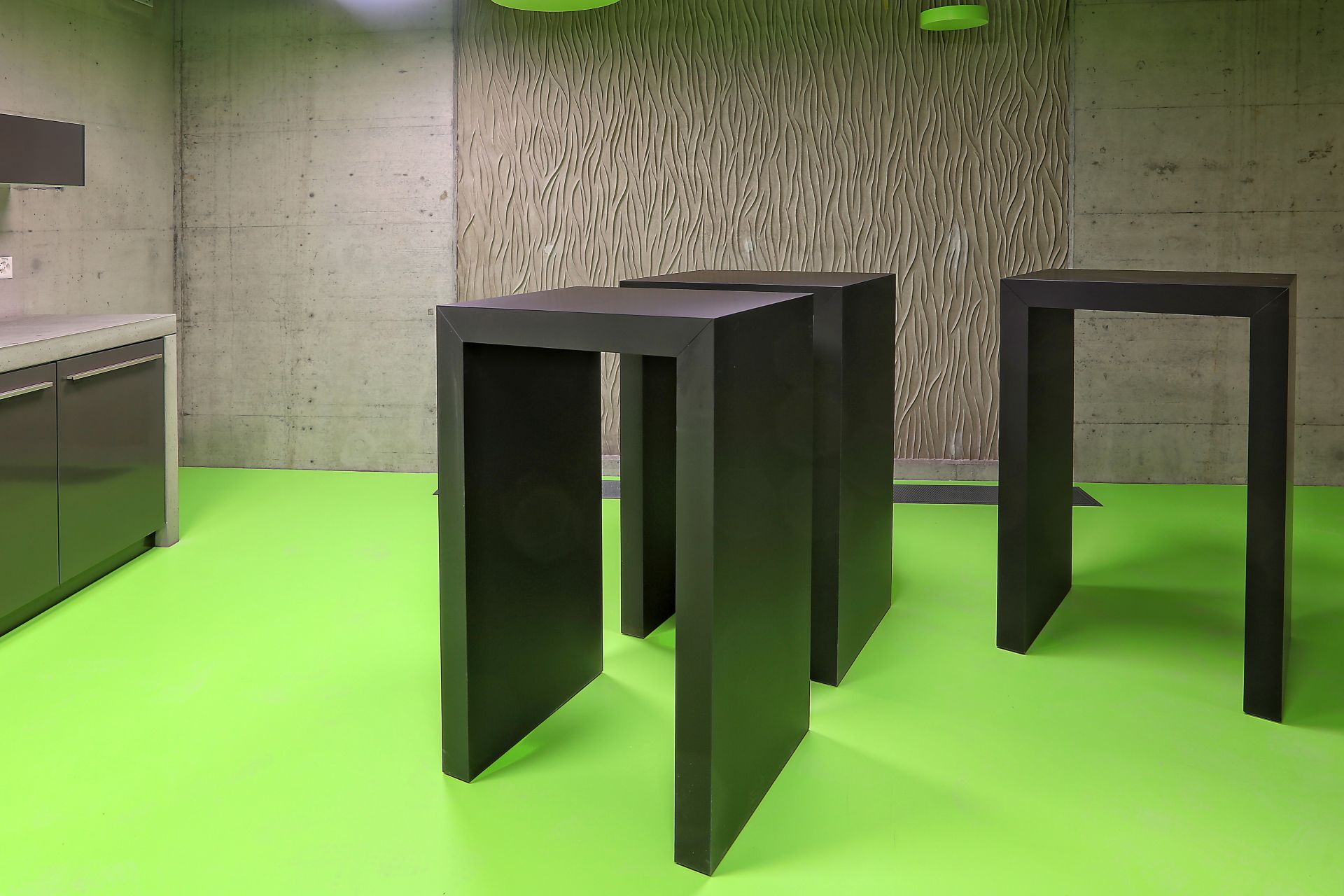 Green floor and architectural concrete wall in a kitchen