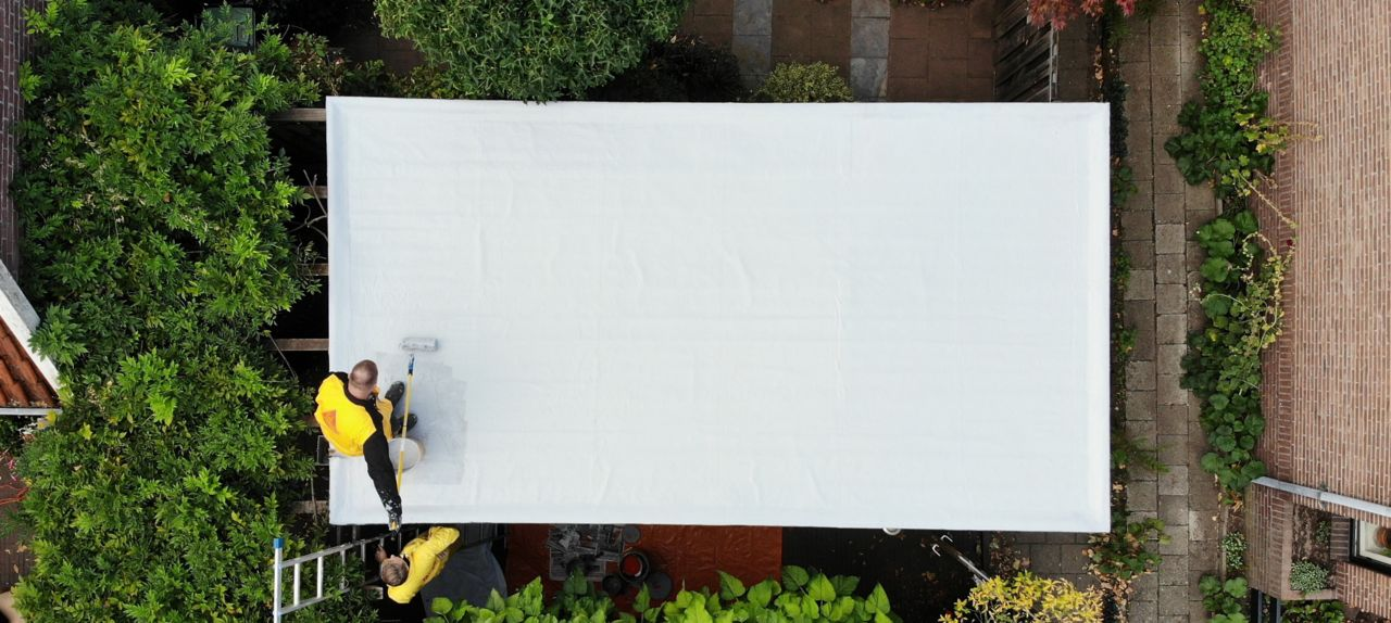 Construction workers applying Sikalastic-580 liquid applied membrane on the roof drone view