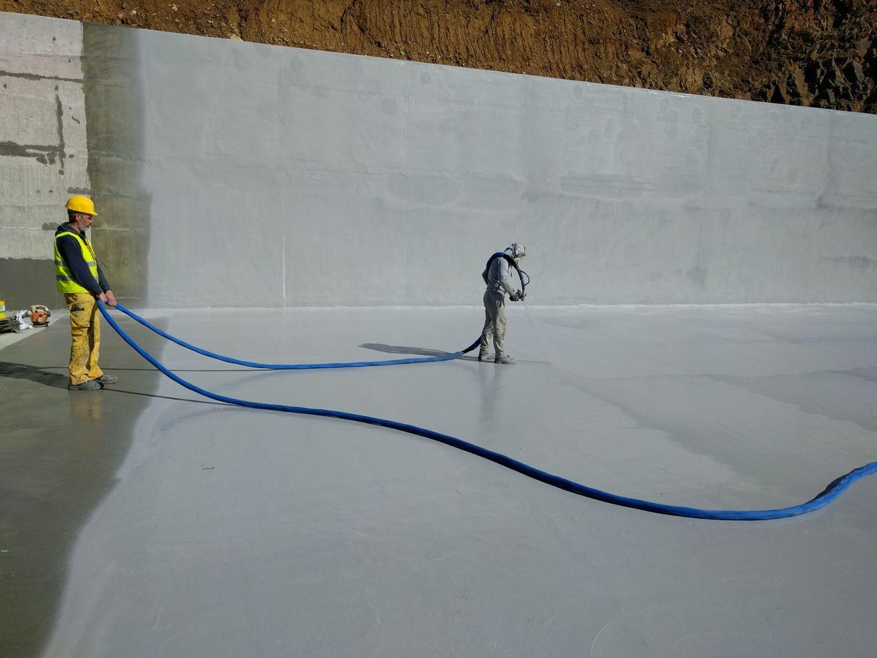 Two men spraying liquid-applied membrane
