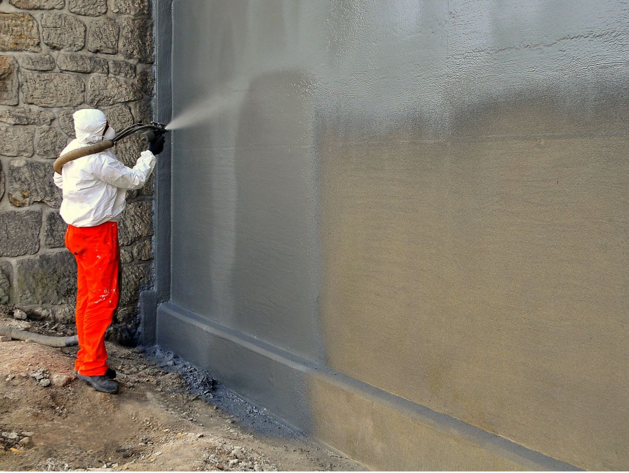 Man spraying liquid-applied membrane on a wall