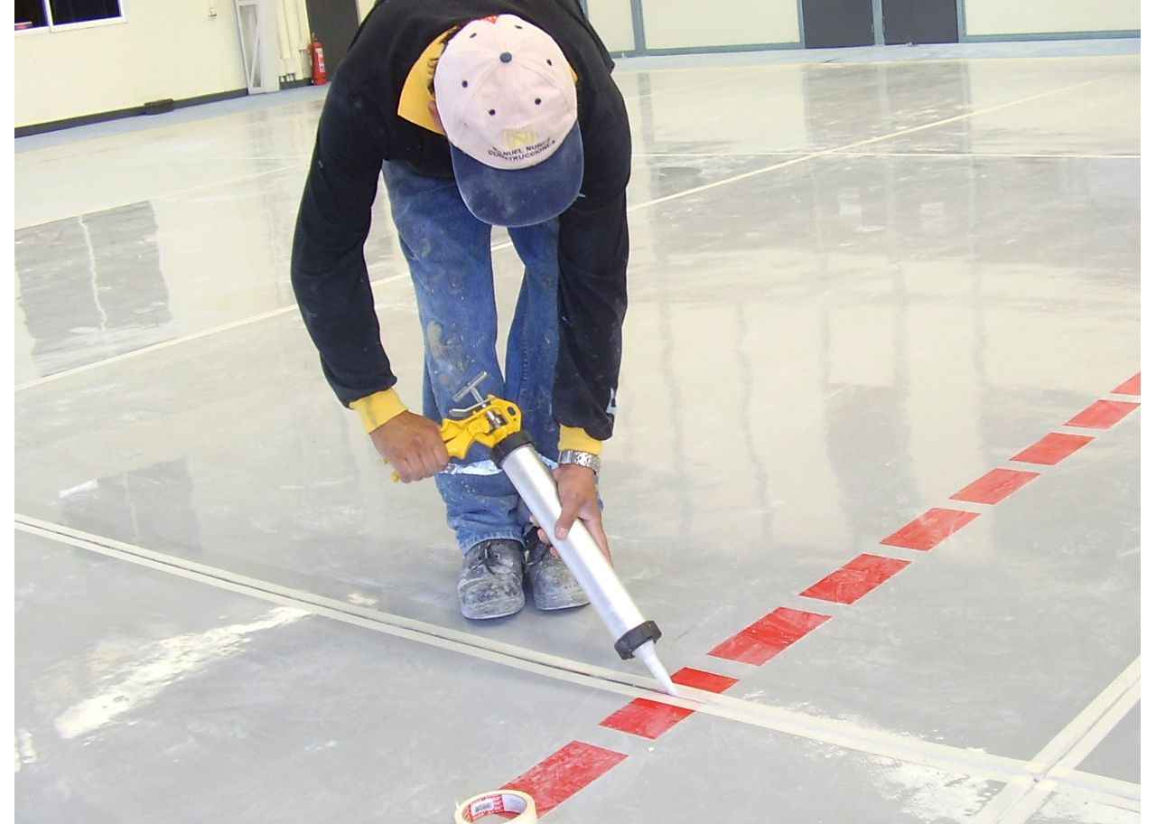 Man applying joint sealant to floor joint with hand applicator gun