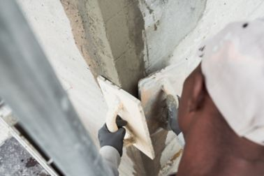 Man repairing concrete wall with Sika repair mortar