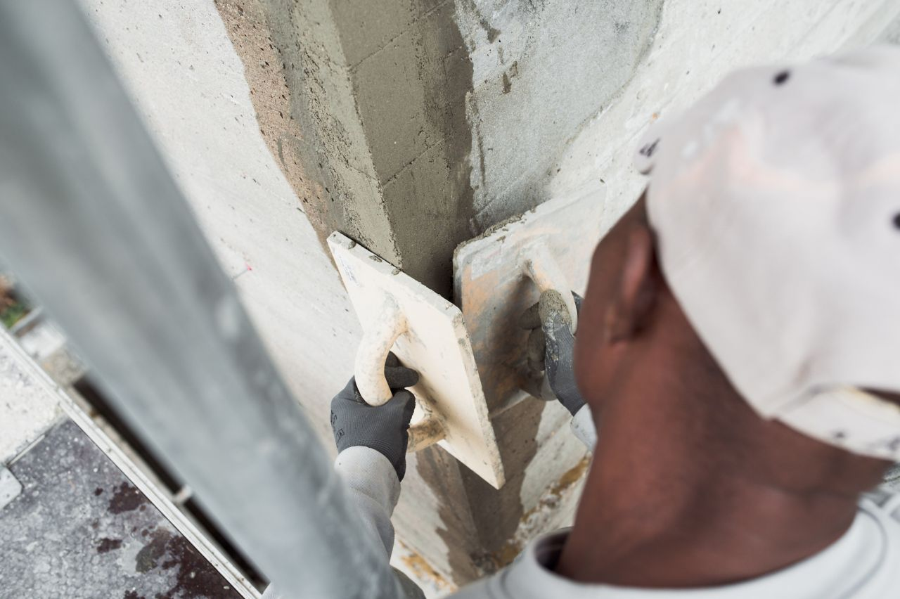 Man repairing concrete wall with Sika repair mortar