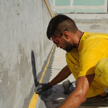Man waterproofing at the Epirus Sport and Health Center in Ioannina, Greece