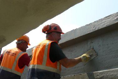 Men repairing concrete bridge with Sika repair mortar