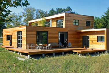 Modular building home with terrace and wood panel facade