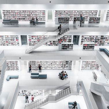 People browsing modern library, photo by Christian Wiediger on Unsplash
