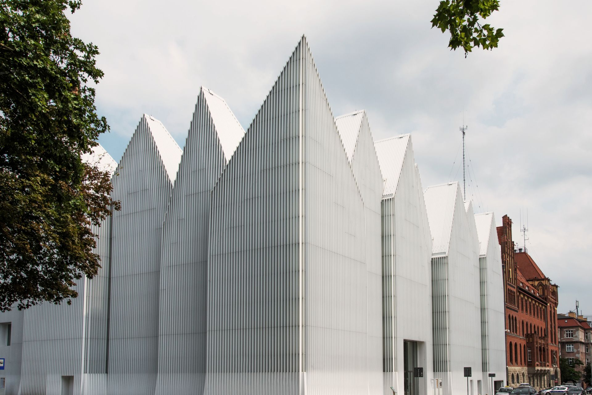 White facade of Szczecin Philharmonic Hall contrasting with old red buildings