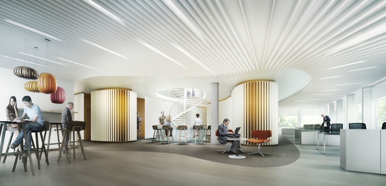 The interior of an office building with people sitting at tables throughout the building