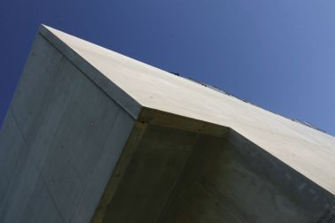 Rigid bonding of prefabricated concrete facade panels to building with architectural smooth concrete and blue sky