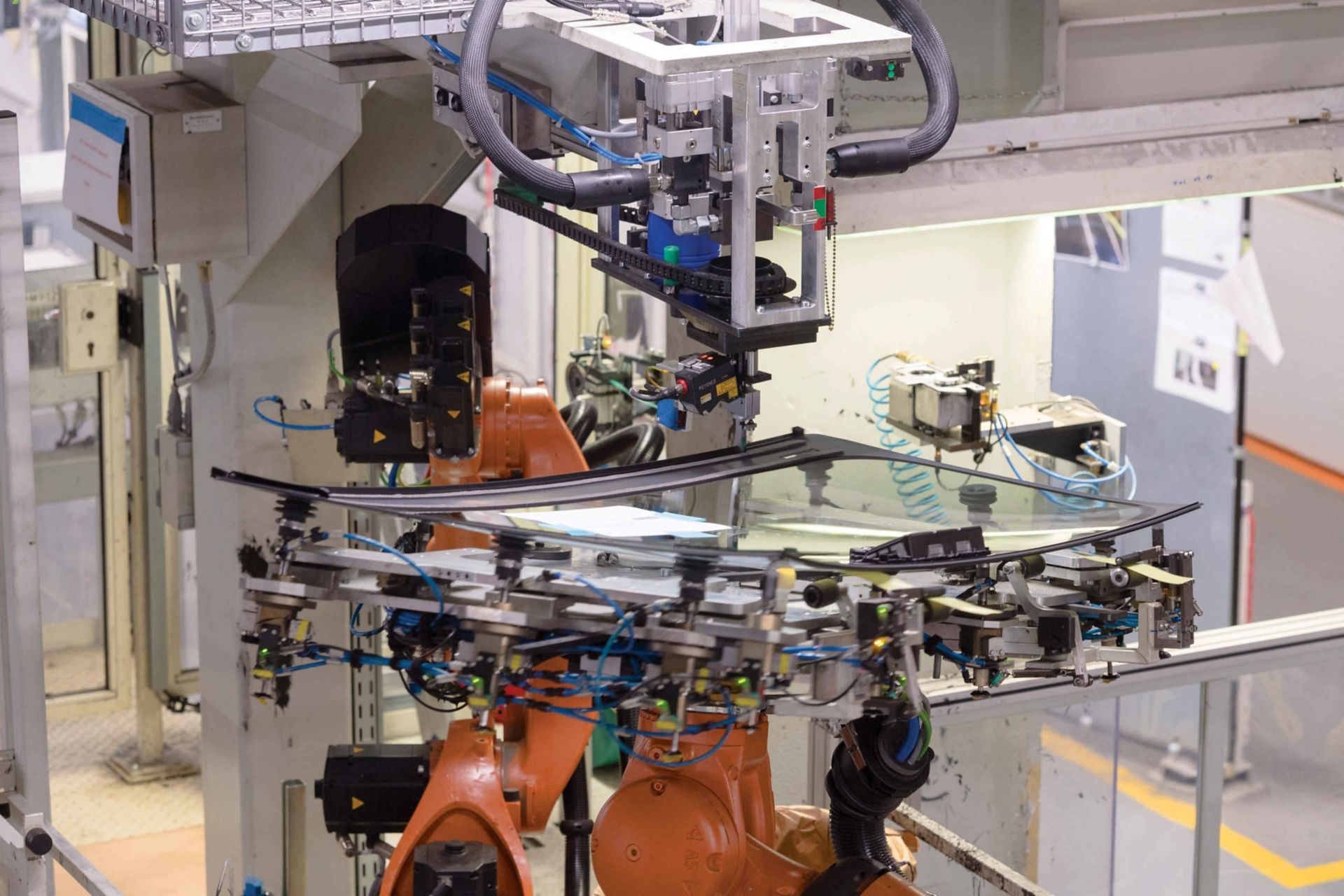 Factory line view of vehicle windshield with Sikaflex Assembly Adhesive being applied