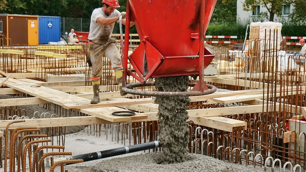 Construction worker pouring ready mix concrete on building basement