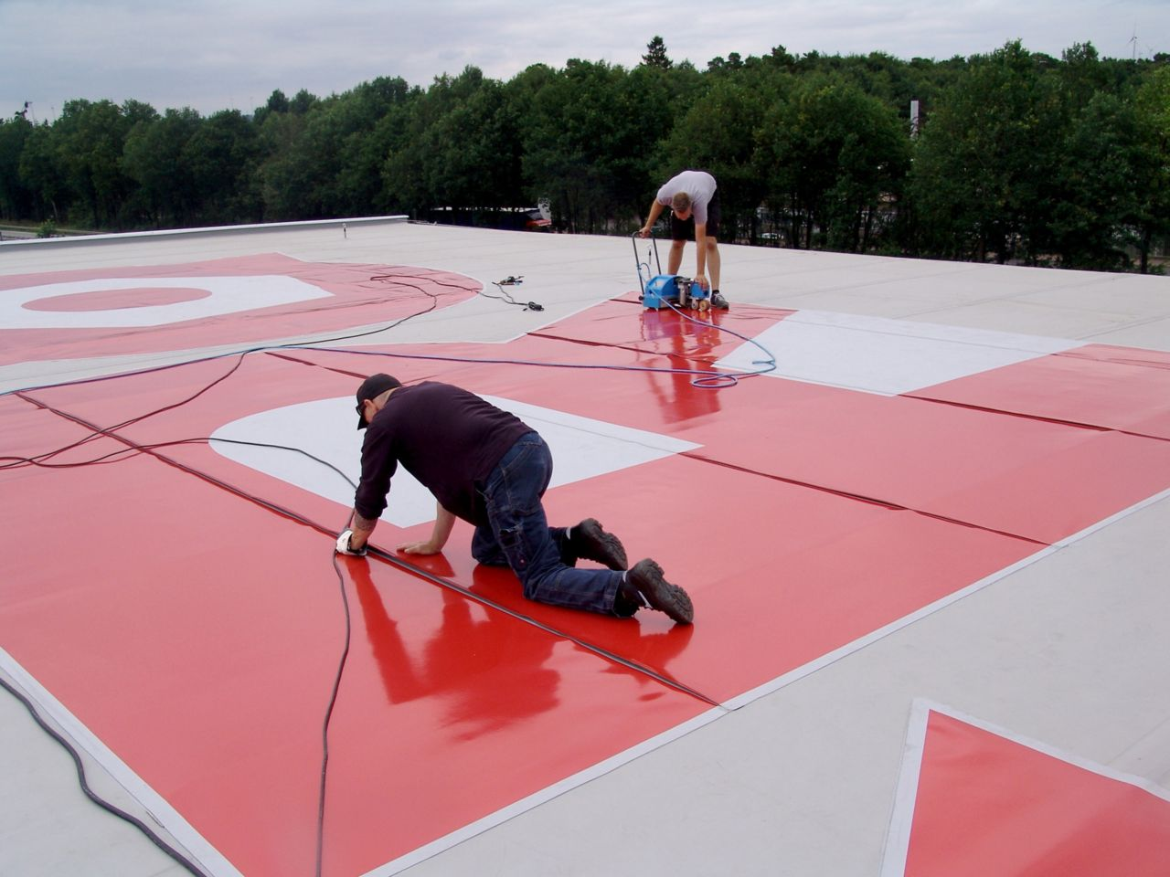 Men welding red colored Sika roof graphic onto roof