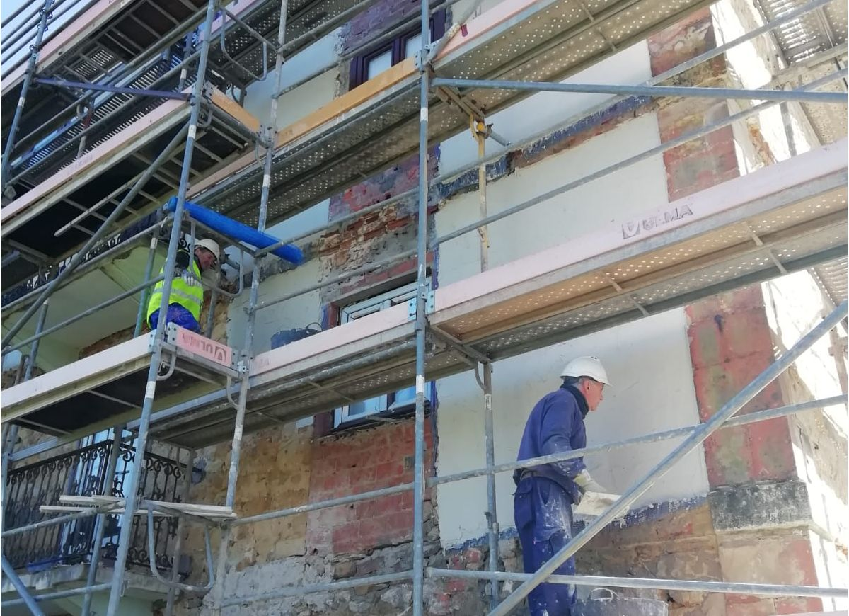 Construction workers applying renovation mortar on wall