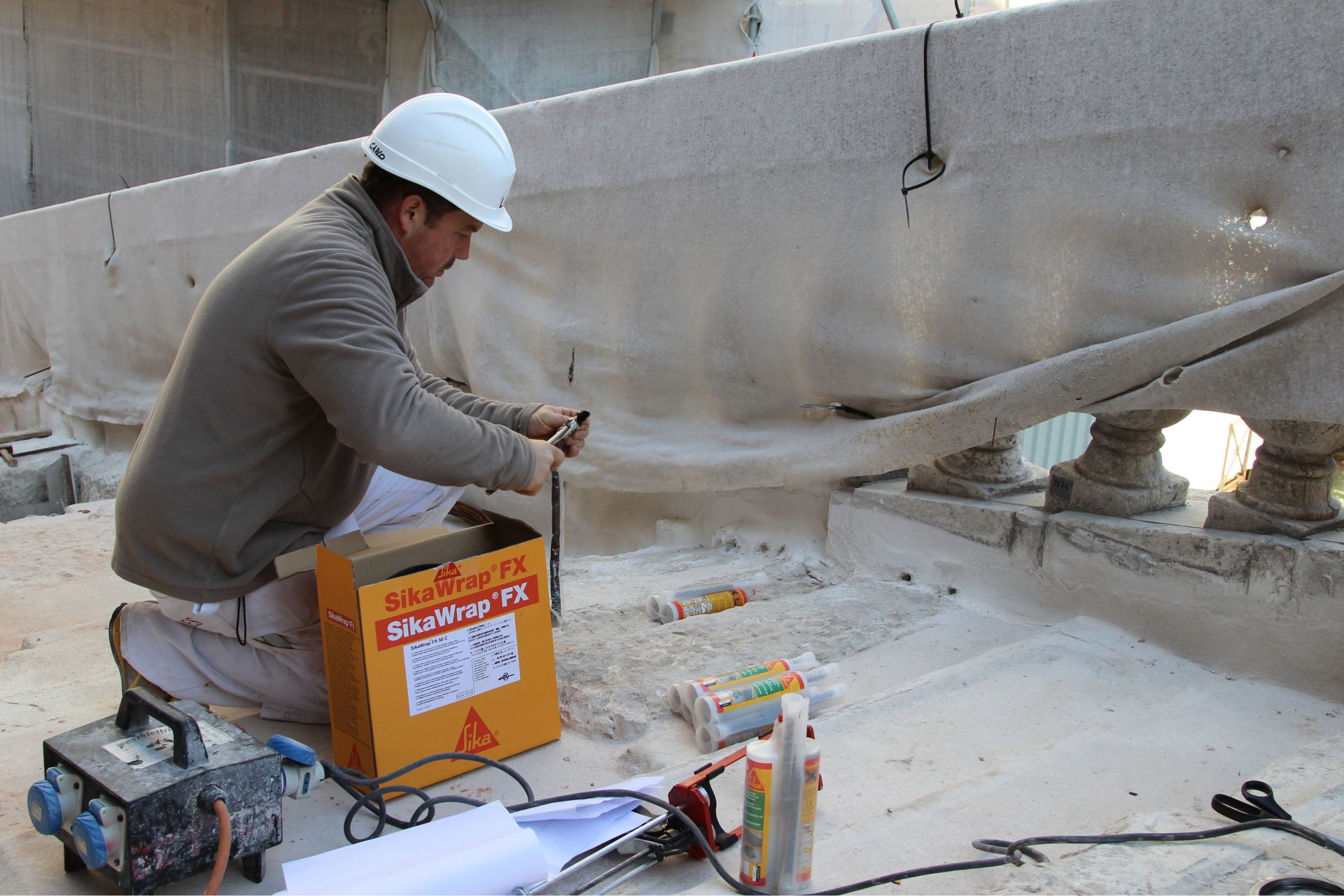 Man repairing Rialto Bridge in Venice Italy with Sika products