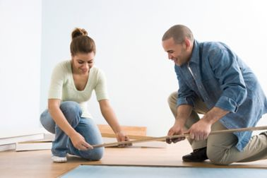 2 people applying a sandwich panel SikaMelt bonded wood floor to the house floor