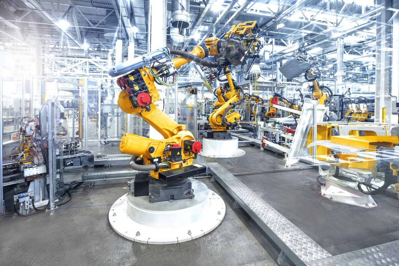 Robotic arms in a car plant manufacturing warehouse