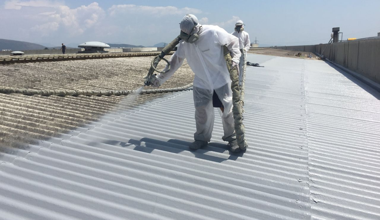 Applicators applying liquid applied membrane to corrugated metal roof in protective clothing