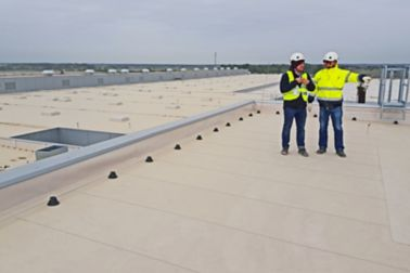 Two construction workers standing on Sarnafil waterproofing membrane on roof of Volkswagen Plant