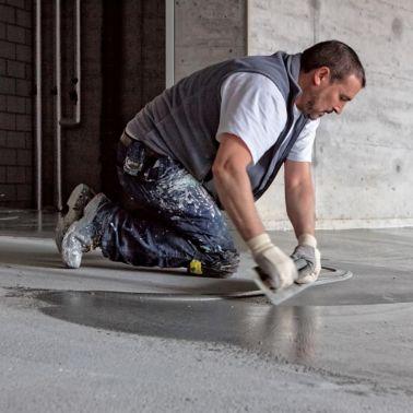 Man applying SikaScreed on floor