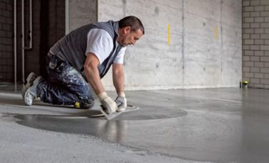 Man applying SikaScreed on floor