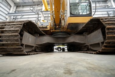 Excavator standing on heavy duty cementitious floor in warehouse