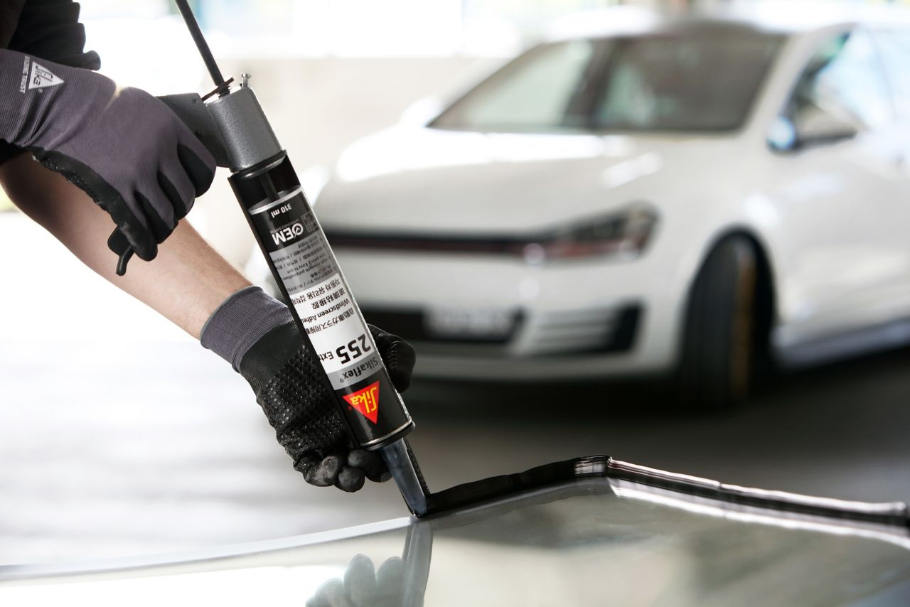 Fitter performing an auto glass replacement with Sikaflex 255 Extra