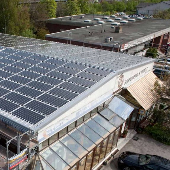 Photovoltaic roof panel system on a commercial building