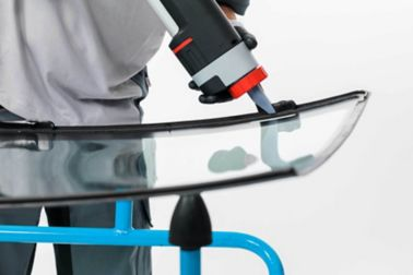 Close up View of technician manually applying Sikaflex glass replacement adhesive on windshield